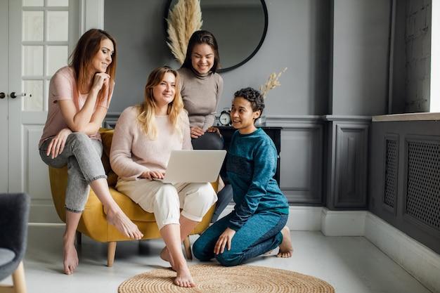 Dziewczyny przyjaźni zakupy online pojęcie. czterech pięknych przyjaciół siedzi w domu i zamawia przez internet.