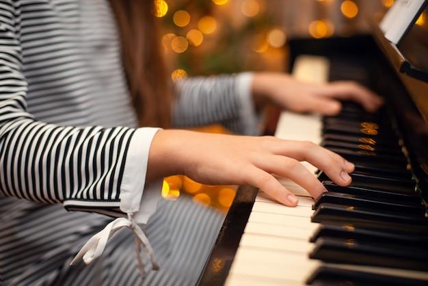 Dziewczyny ręce na pianinie, zbliżenie, piękny bokeh w tle, kobieta grająca na pianinie. świąteczne lampki i muzyka, koncert, czas rodzinny, koncepcja wakacji.