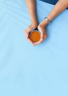 Dziewczyny ręce trzymają filiżankę herbaty na niebieskim tle. biurko do domowego biura. widok płaski, widok z góry. wygląd bloga modowego. dodaj swój tekst.
