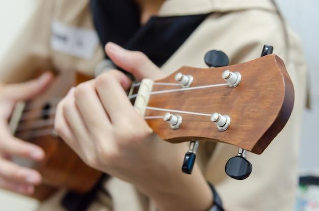Dziewczyny ręka bawić się ukulele