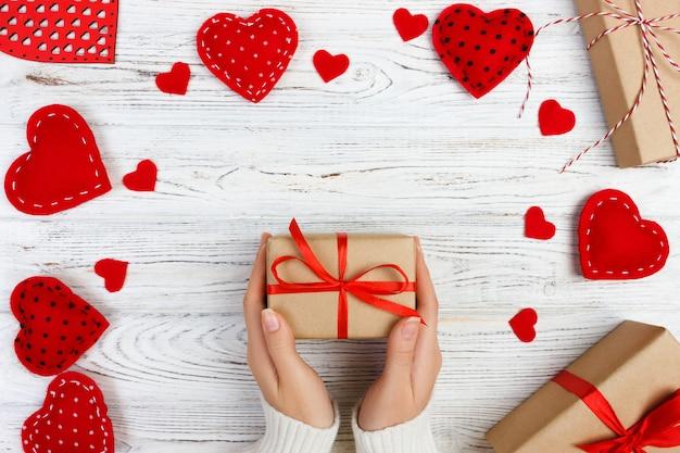 Dziewczyny ręka daje valentine prezenta pudełku z czerwonym sercem inside na białym starym drewnianym stole. walentynki