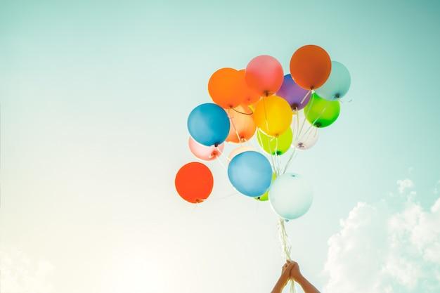 Dziewczyny ręka trzyma multicolor balony