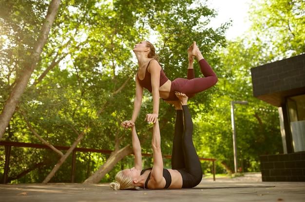 Dziewczyny robią ćwiczenia równowagi na grupowym treningu jogi w letnim parku