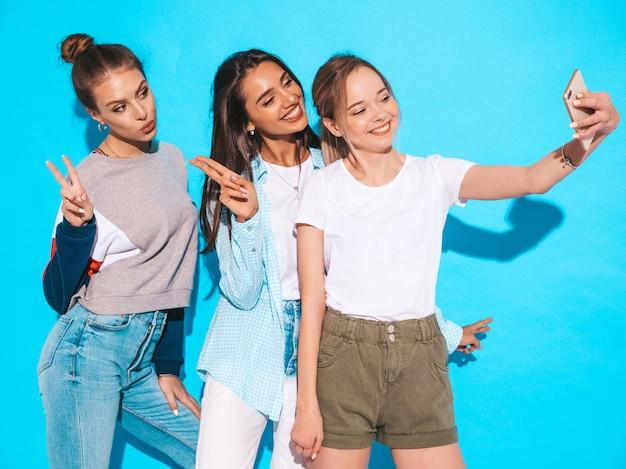 Dziewczyny robią selfie autoportretowi fotografiom na smartphone modele pozuje blisko błękit ściany w studiu, kobieta pokazuje pozytywne twarzy emocje