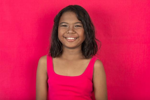 Dziewczyny robią zdjęcia twarzy i patrzą w kamerę. jasne i urocze. ubrana w różową koszulę i szarą scenę.