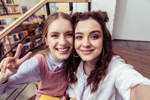 Dziewczyny robią zdjęcie. śliczne piękne dziewczyny o nieskazitelnej skórze robią selfie i pokazują twarze