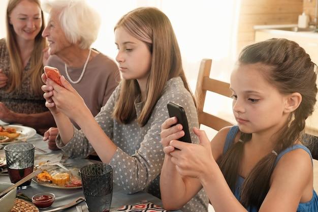 Dziewczyny rozmawiają online za pomocą smartfonów, siedząc z rodziną przy stole podczas kolacji