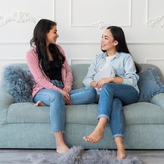 Dziewczyny rozmawiają siedząc na kanapie