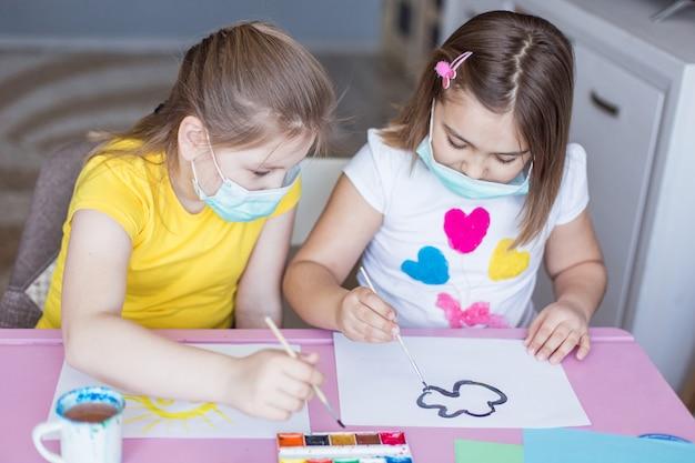 Dziewczyny rysujące razem w domu podczas kwarantanny w sterylnych maskach. gry z dzieciństwa, rysunek sztuki, koncepcja pobytu w domu