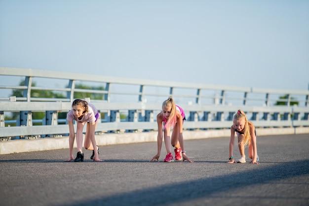 Dziewczyny rywalizują na asfaltowej drodze na tle wieczornego nieba