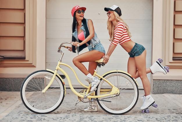 Dziewczyny się bawią. widok z boku szczęśliwej młodej kobiety jadącej na rowerze, podczas gdy jej koleżanka jeździ na łyżwach za nią