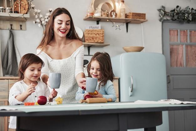 Dziewczyny się uśmiechają. młoda piękna kobieta daje dzieciom napoje, gdy siedzą przy stole z zabawkami.