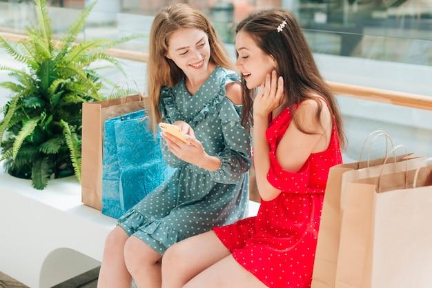 Dziewczyny siedzą i rozmawiają w centrum handlowym