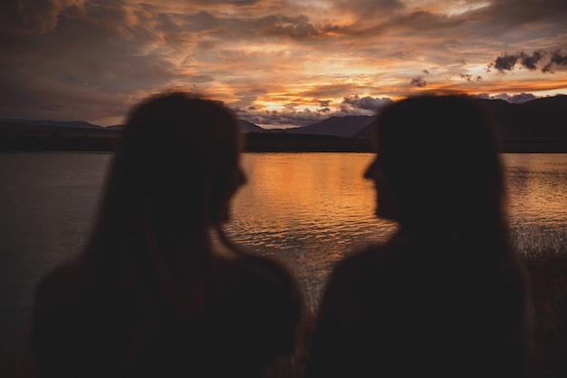 Dziewczyny siedzą na brzegu podczas zachodu słońca nad jeziorem polka w nowej zelandii