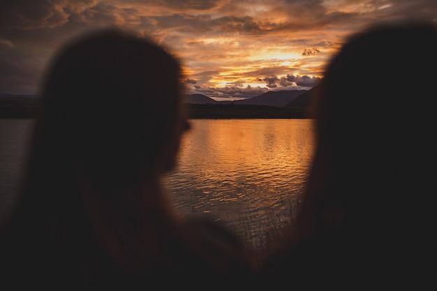 Dziewczyny siedzą na brzegu podczas zachodu słońca w jeziorze polka w nowej zelandii