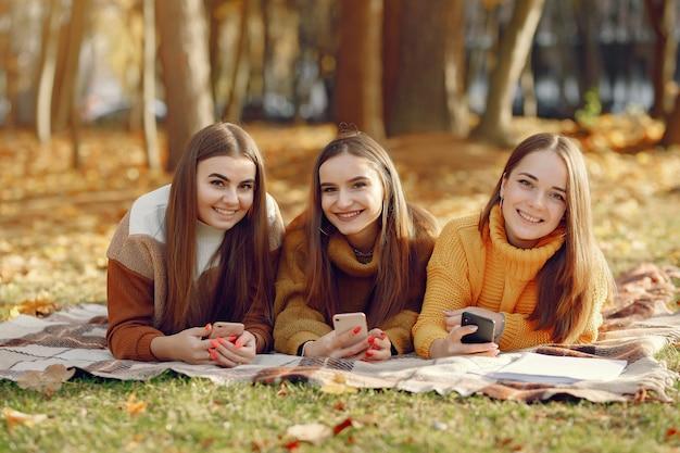 Dziewczyny siedzą na kocu w parku jesienią