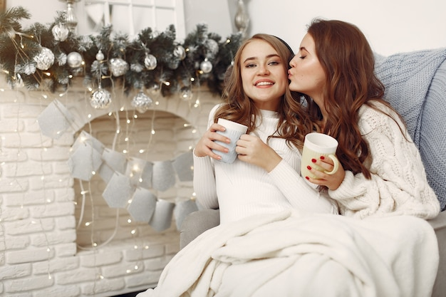 Dziewczyny siedzą na krześle. kobiety z kubkami. siostry przygotowują się do świąt