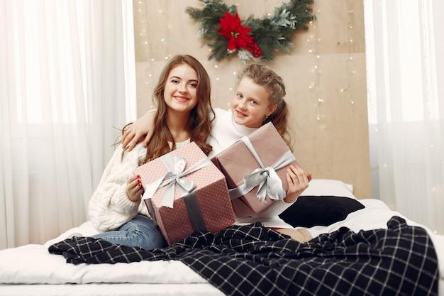 Dziewczyny siedzą na łóżku kobiety z prezentem piękności przygotowują się do świąt