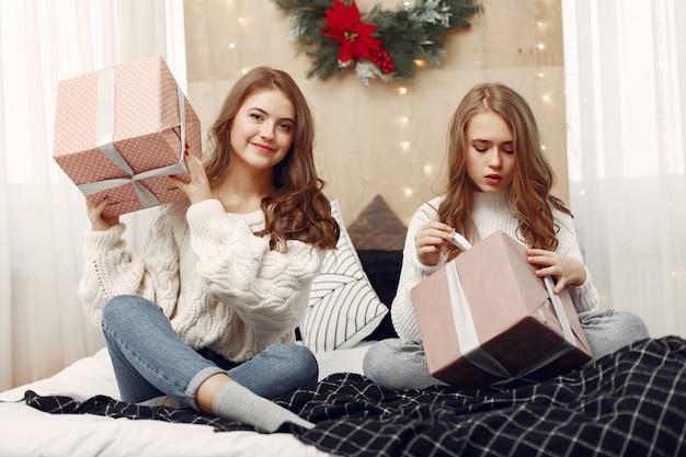 Dziewczyny siedzą na łóżku. kobiety z pudełkami na prezenty. przyjaciele przygotowują się do świąt.