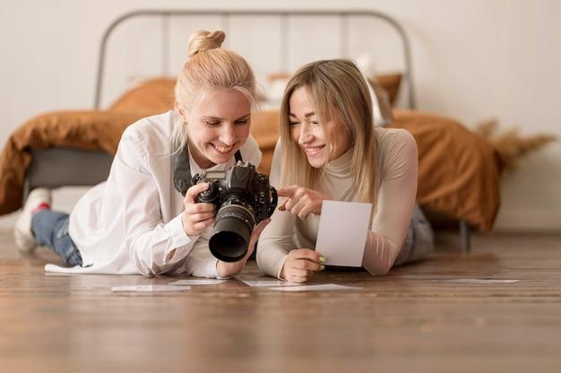Dziewczyny siedzą na podłodze i patrzą na zdjęcia