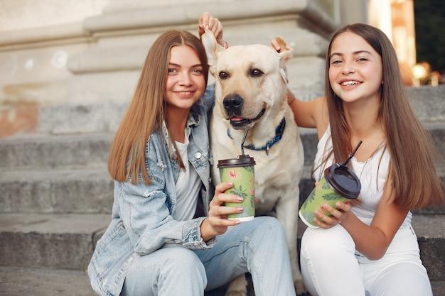 Dziewczyny siedzą na schodach z uroczym psem