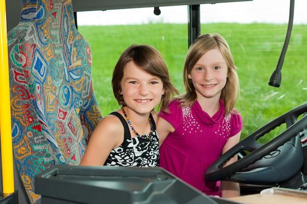 Dziewczyny siedzą na siedzeniu kierowcy autobusu