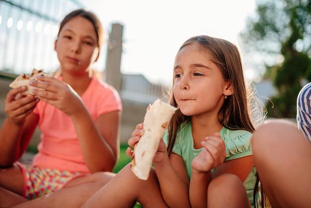 Dziewczyny siedzą na zewnątrz na ziemi i jedzą kanapki