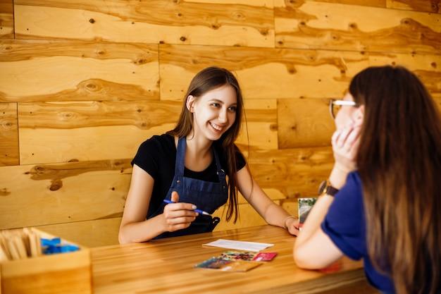 Dziewczyny siedzą przy drewnianym stole w kawiarni