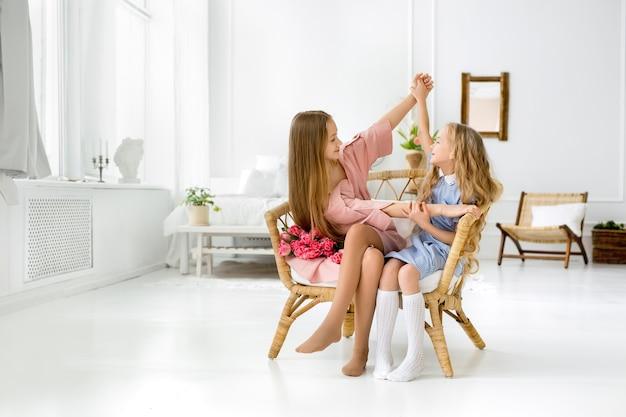 Dziewczyny siedzą razem na krześle w pokoju z bukietem tulipanów.