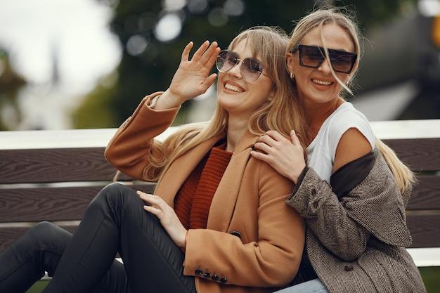 Dziewczyny siedzą w wiosennej pogodzie i trzymają w dłoni kawę