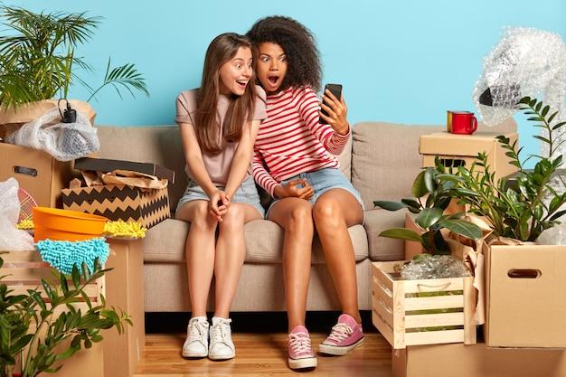 Dziewczyny siedzące na kanapie otoczonej pudełkami