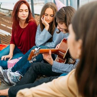 Dziewczyny słuchają chłopca grającego na gitarze. styl życia muzyki artystycznej. urzekające dźwięki romantycznego występu