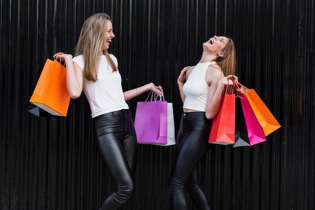 Dziewczyny śmieją się, trzymając torby na zakupy