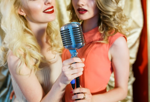 Dziewczyny śpiewają karaoke w restauracji.