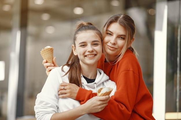 Dziewczyny stojące w letnim mieście z lodami