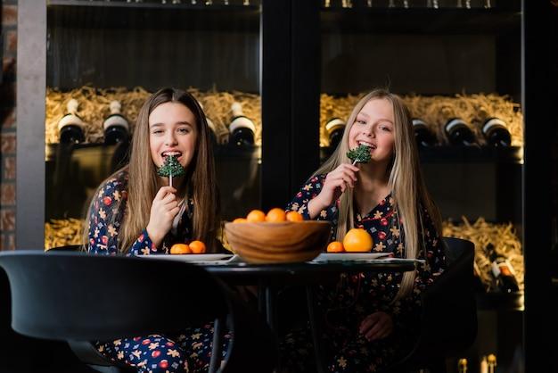 Dziewczyny świętują nowy rok i boże narodzenie i jedzą mandarynki na łóżku. są prezenty i zdobione gałęzie jodły ze złotymi kulkami.