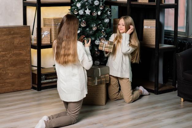 Dziewczyny świętują sylwestra i boże narodzenie i jedzą mandarynki na łóżku. są prezenty i zdobione gałązki jodły ze złotymi kulkami.