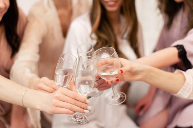 Dziewczyny świętują wieczór panieński panny młodej. dziewczyny brzęczą kieliszkami wina.