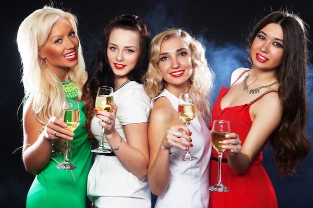 Dziewczyny szczękają flety z winem musującym
