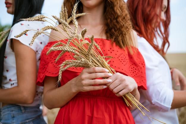 Dziewczyny trzymają kłosy pszenicy w dłoniach zbliżenie