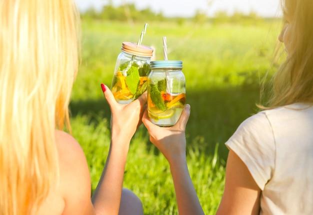 Dziewczyny trzymają świeżą lemoniadę w słoikach ze słomkami. hipster letnia impreza z napojami. zdrowy wegański styl życia. ekologiczny w naturze. cytryny, pomarańcze i jagody z miętą w szklance.