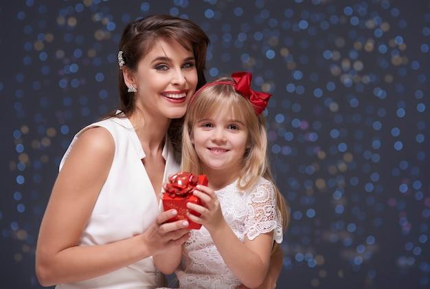 Dziewczyny trzymające jeden mały prezent gwiazdkowy