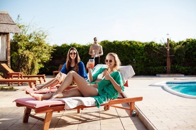 Dziewczyny uśmiechają się, piją koktajle, opalają się, leżą w pobliżu basenu