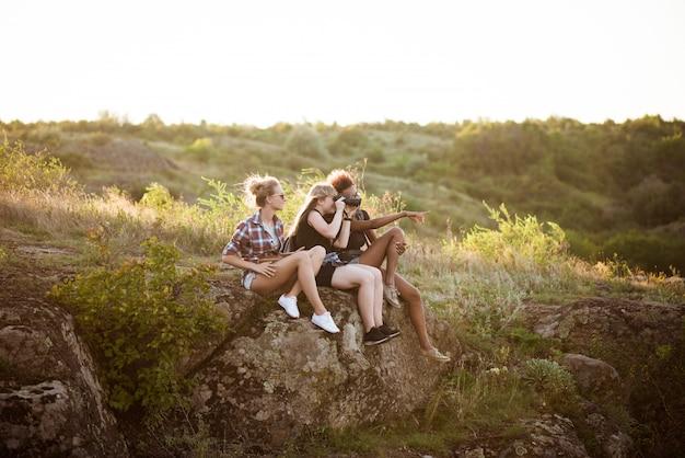 Dziewczyny uśmiechnięte, siedząc na skale, ciesząc się widokiem w kanionie