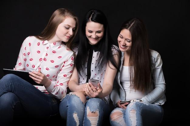 Dziewczyny uśmiechnięte whilen patrząc na telefon komórkowy