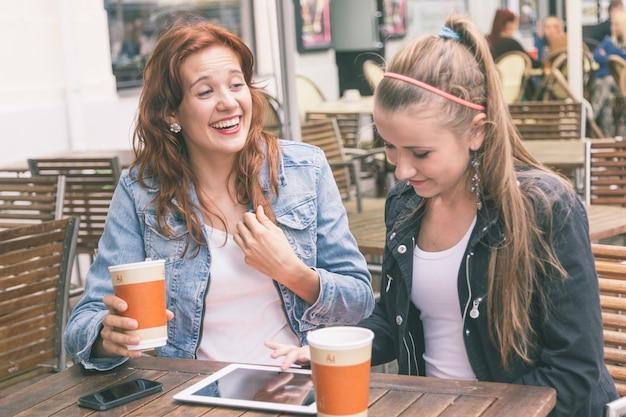 Dziewczyny używa cyfrowej pastylkę przy kawiarnią
