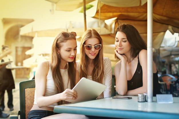 Dziewczyny używające tabletu na tarasie bistro