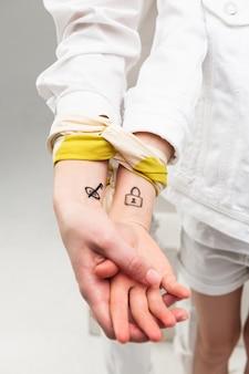 Dziewczyny w białych ciuchach z obrazkami na nadgarstkach i łączące ręce kolorowym szalikiem