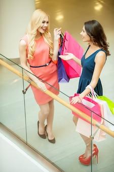 Dziewczyny w centrum handlowym. widok z góry dwóch przyjaciół trzymających torby na zakupy i rozmawiających, stojąc w centrum handlowym