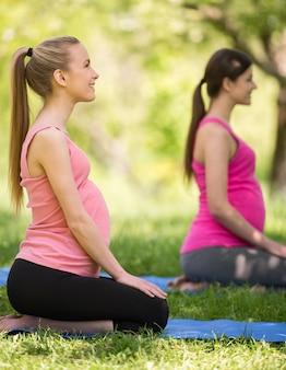 Dziewczyny w ciąży klęczą w naturze i odpoczywają.